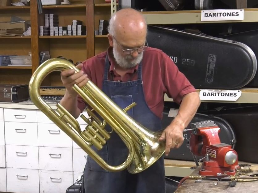 Instrumental repair department staff fixes a horn.