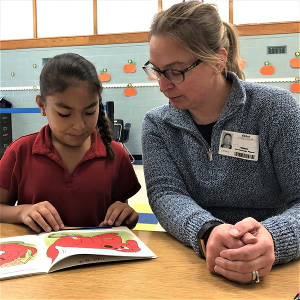 Community volunteer reads with second grade student at Minneha
