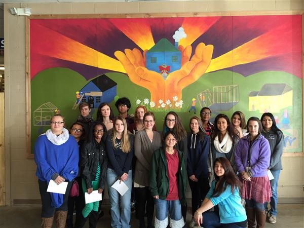 Student artists by mural installed at the Wichita's Habitat for Humanity Re-Store