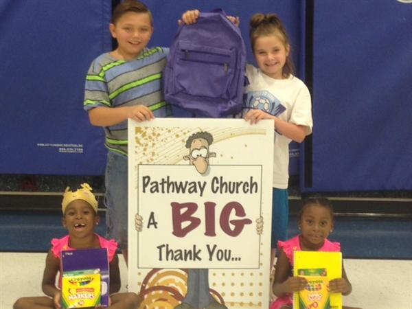 Students show off the backpacks donated by a local church.